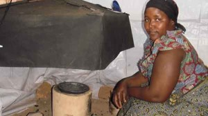 A local cook preparing soup for a CCT of a sunken pot mud stove in Rwanda.