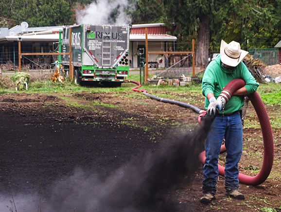 Man in cowboy hat blows compost onto field