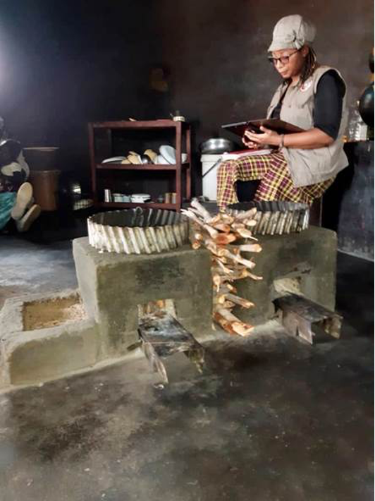 A woman sits next to two rocket stoves.